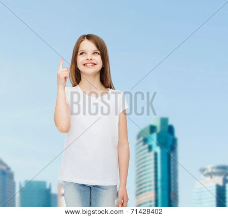 advertising, childhood, city, gesture and people concept - smiling girl in white t-shirt pointing finger up over business center background