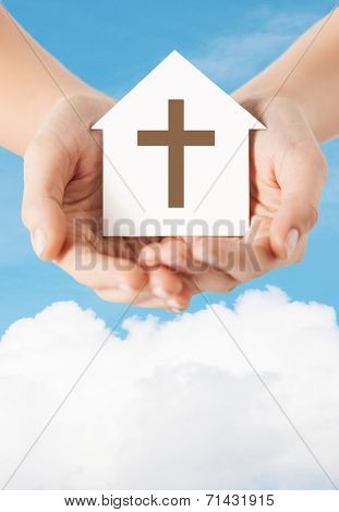 religion, christianity and charity concept - close up of woman hands holding paper house with christian cross symbol over blue sky with white cloud background