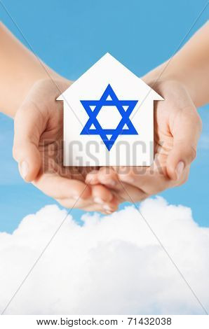 religion, judaism and charity concept - close up of woman hands holding house with star of david over blue sky with white cloud background