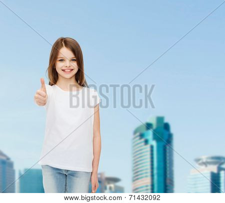 advertising, childhood, city, gesture and people concept - smiling girl in white t-shirt showing thumbs up over business center background