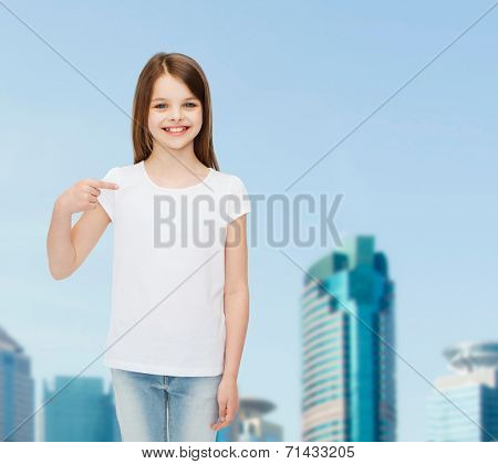 advertising, childhood, gesture and people concept - smiling girl in white shirt pointing finger on herself over business center background