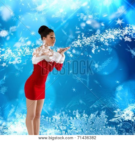 Pretty santa girl blowing over her hands against blue snow flake pattern design