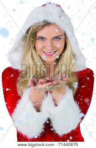 Pretty girl in santa outfit with hands out against snow falling