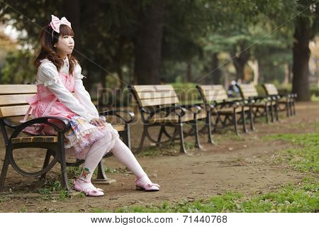 Japanese girl in lolita cosplay fashion sitting on a bench, Tokyo