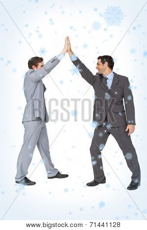 Unified business team high fiving each other against snow falling