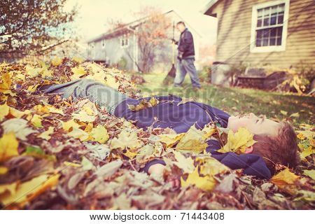 Young boy daydreaming in a pile of fall leaves while his father