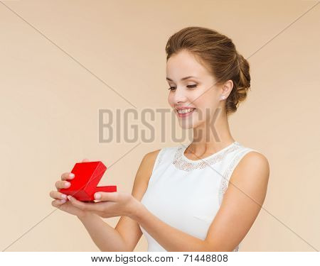 holidays, presents, wedding and happiness concept - smiling woman in white dress holding red gift box over beige background