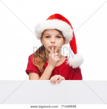 christmas, xmas, holidays and advertisement concept - happy girl child in santa helper hat with blank white board making shh gesture