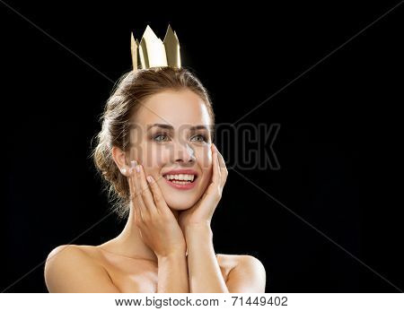 people, holidays, royalty and glamour concept - laughing woman wearing golden crown over black background
