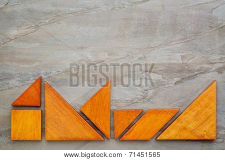 seven tangram wooden pieces, a traditional Chinese puzzle game,  on a slate rock  background with a copy space