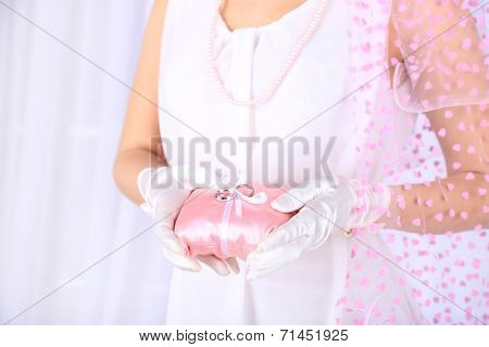 Bride in white dress and gloves holding decorative pillow with wedding rings, close-up