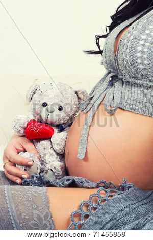 Close Up Of Pregnant Belly. Woman Expecting A Baby With A Cute Teddy Bear.