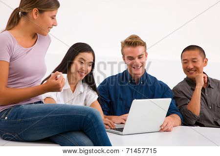 Group Of Happy Friends Using Laptop