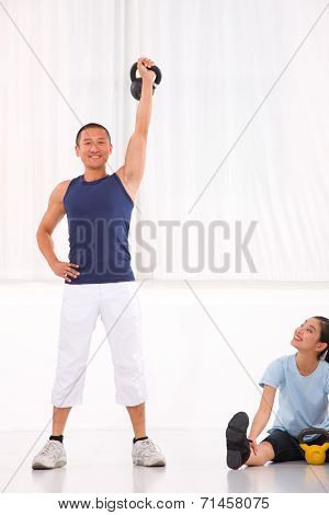 Asian Woman Looking Man Doing Kettle Bell Exercise