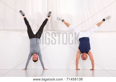 Man And Woman Doing Handstand Exercise In Gym