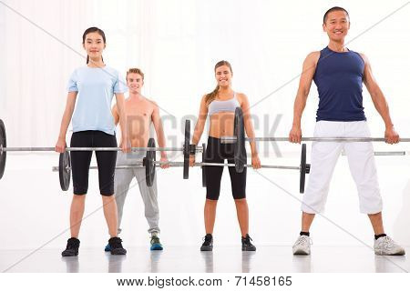 Multiethnic Group Of People Exercising With Weightlifting Bar In Gym