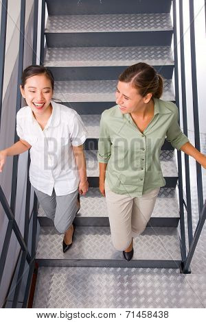 Two Multiethnic Young Woman Moving Staircase