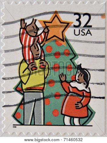 A stamp printed in USA shows a family decorating a christmas tree