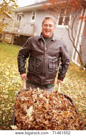 Senior man cleaning up fall leaves