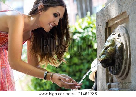 Beautiful Woman Drinks Water From Source In Summer City Park.