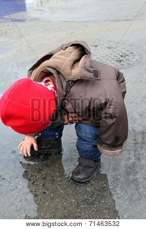 Child with red hat playing in the puddle of water