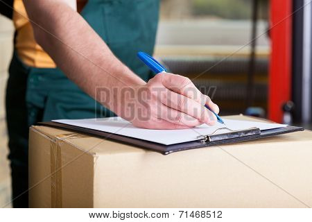 Man's Hand Signing Delivery Document