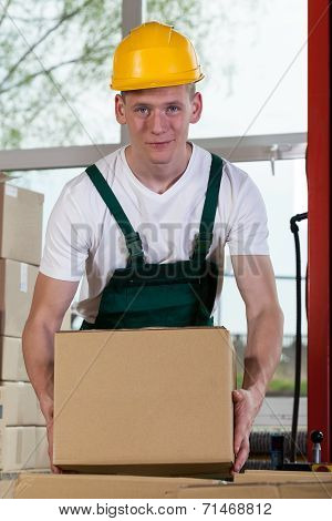 Portrait Of A Warehouse Worker Lifting A Box