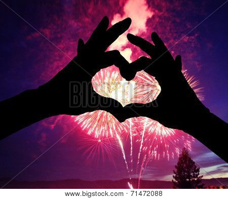 a silhouette of hands shaped in a heart against a 4th of july fireworks background