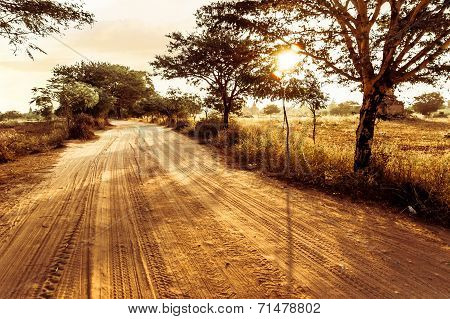 Empty Road Going Through Rural Landscape Under Sunset Sky With Sun Beams. Dry Season In Southeast