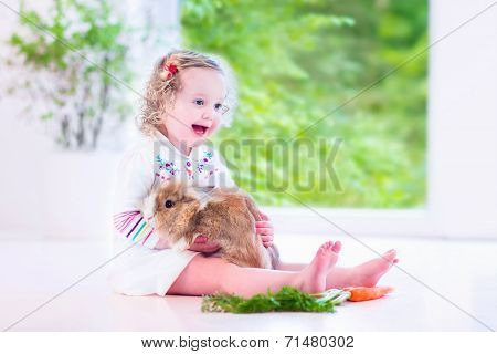 Little Girl Playing With A Bunny