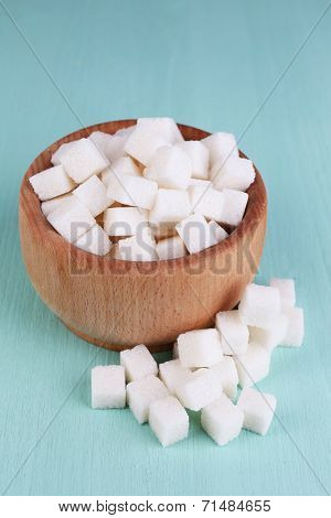 White refined sugar in wooden bowl on color wooden background