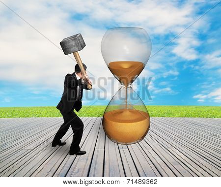 businessman hand hold hammer to hit hour glass