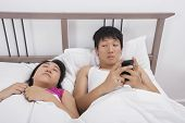 pic of adultery  - Man using cell phone while looking at woman sleeping in bed - JPG