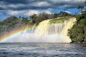 stock photo of canaima  - waterfall and a rainbow in front of it on a bright hot day in Venezuela - JPG