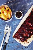 pic of baby back ribs  - Barbecue ribs with fires and sauce on blue wooden table - JPG