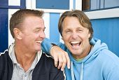 stock photo of gay couple  - A colour portrait photo of a happy laughing gay male couple having fun together while sitting in front of some beach huts - JPG