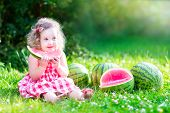 pic of watermelon  - Funny little girl adorable toddler with curly hair wearing a red dress eating watermelon healthy fruit snack playing in a sunny garden on a hot summer day - JPG