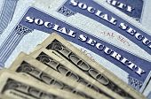 stock photo of social-security  - Detail of several Social Security Cards and cash money symbolizing retirement pensions financial safety - JPG