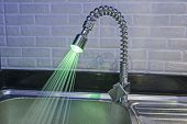 foto of tapping  - Ornate illuminated luxury tap faucet with green light and water running in apartment kitchen - JPG