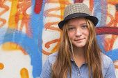 picture of mural  - Young nice fashionable girl in a straw hat near the mural wall - JPG