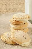 picture of shortbread  - Shortbread cookies with frosting and raspberry bits and a glass of milk - JPG