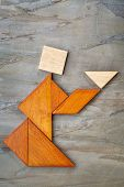 picture of tangram  - abstract picture of a figure offering a cup of tea or soup built  from seven tangram wooden pieces against slate rock - JPG