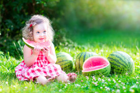pic of eat grass  - Funny little girl adorable toddler with curly hair wearing a red dress eating watermelon healthy fruit snack playing in a sunny garden on a hot summer day - JPG