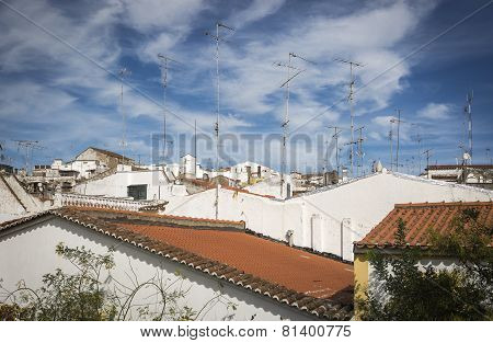 TV antennas, roofs in white houses and a blue sky