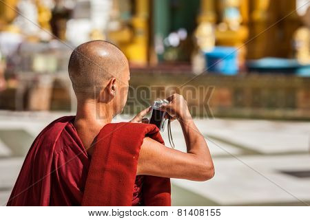 YANGON, MYANMAR - JANUARY 3, 2014: Buddhist monk taking photos with digital point-and-shoot camera in Shwedagon Paya pagoda