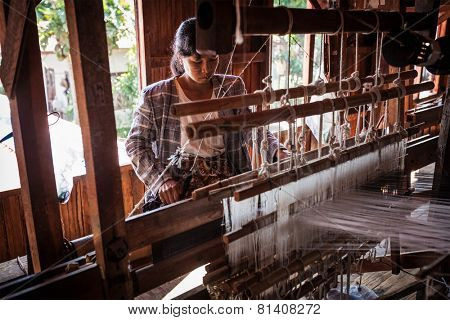 INLE LAKE, MYANMAR - JANUARY 8, 2014: Burmese woman weaves fabric at weaving factory where textile is manufactured in traditional way