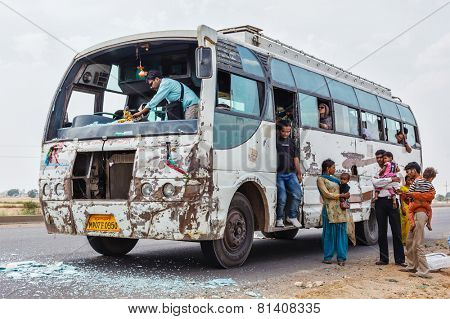 MADHYA PRADESH, INDIA - APRIL 12, 2011: Indian bus driver cleaning shattered windshield glass after traffic accident. The rate of traffic accidents in India is amongst the highest in the world