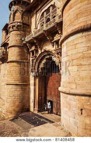 GWALIOR, INDIA - APRIL 11, 2011: Man with bicycle coming through door in huge gates of Gwalior Fort - 8th-century hill fort that houses many historic monuments including palaces, temples and water