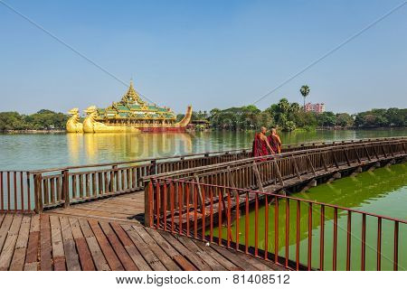 YANGON, MYANMAR - JANUARY 3, 2014:  Two Buddhist monks walking on wooden bridge at at Kandawgyi Lake with Karaweik barge in Background