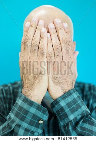 Senior Arabic Pakistani man with hands on face